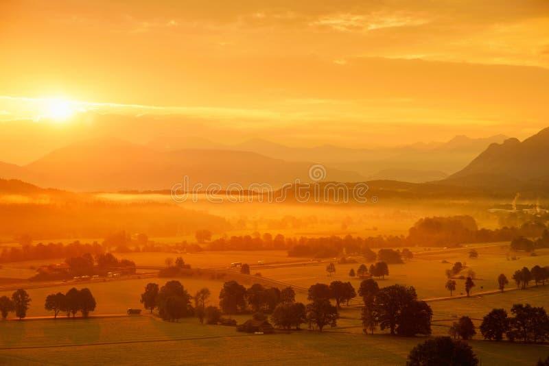Lansdcape strabiliante di mattina di piccolo villaggio bavarese coperto in nebbia Vista scenica delle alpi bavaresi ad alba con i immagine stock libera da diritti