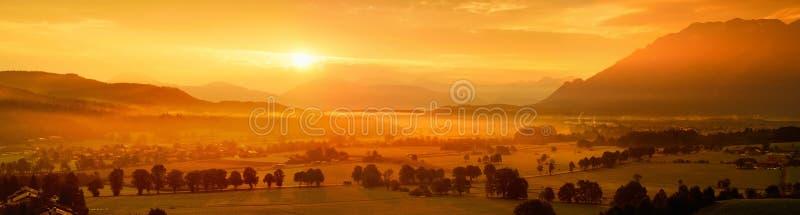 Lansdcape stupéfiant de matin du petit village bavarois couvert en brouillard Vue scénique des Alpes bavarois au lever de soleil  images libres de droits