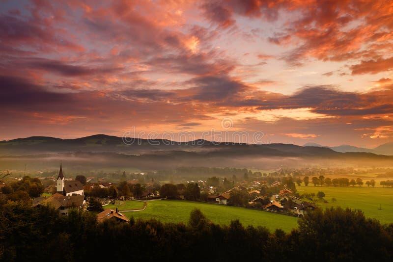 Lansdcape stupéfiant de matin du petit village bavarois couvert en brouillard Vue scénique des Alpes bavarois au lever de soleil  images stock