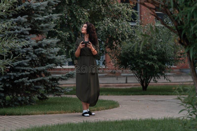Lanserande surrquadcopter för ung härlig kvinna på stads- bakgrund arkivfoto