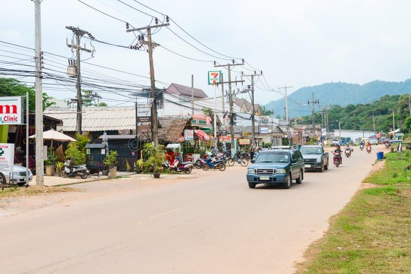 Cars and motorbikes on the main Koh Lanta island road. LANTA, KRABI, THAILAND - 17 OCT 2014: Cars and motorbikes on the main Koh Lanta island road with shops and stock photography