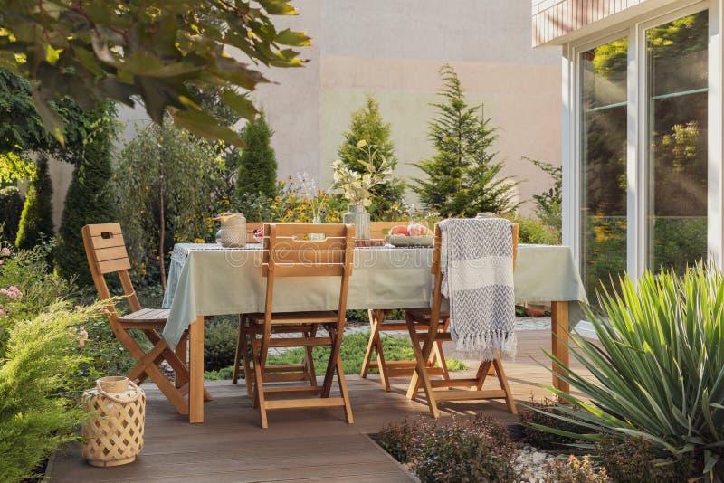 Lantaarn naast stoelen en lijst aangaande het terras van huis met installaties en deken Echte foto royalty-vrije stock foto