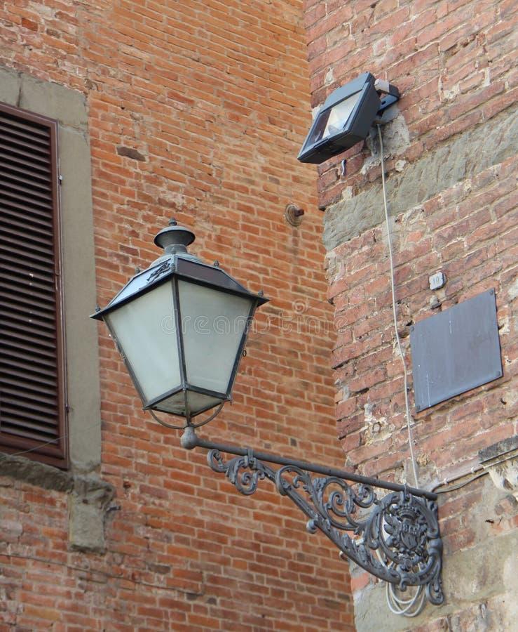 Lantaarn op de achtergrond van een bakstenen muur in de stad van Luca, Italië stock foto