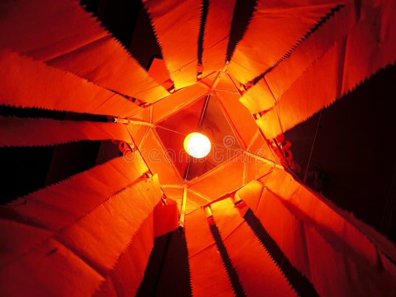 Lantaarn van saffraan de rode kandeel met gloeilamp binnen lantaarn & heldere oranje document staarten royalty-vrije stock afbeelding