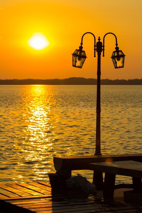 Lantaarnpaal met rivier en zonsondergang stock afbeelding