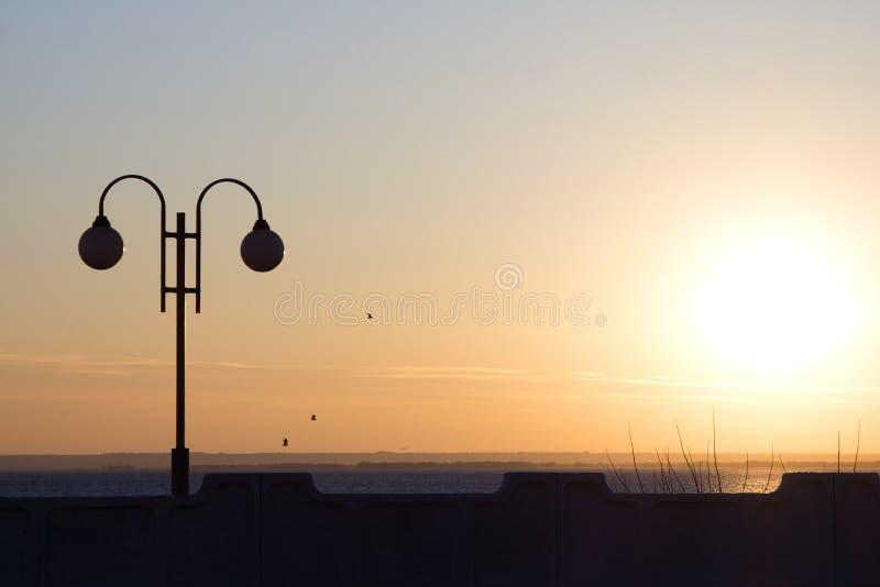 Lantaarnsilhouet bij zonsondergang dichtbij het water stock afbeelding