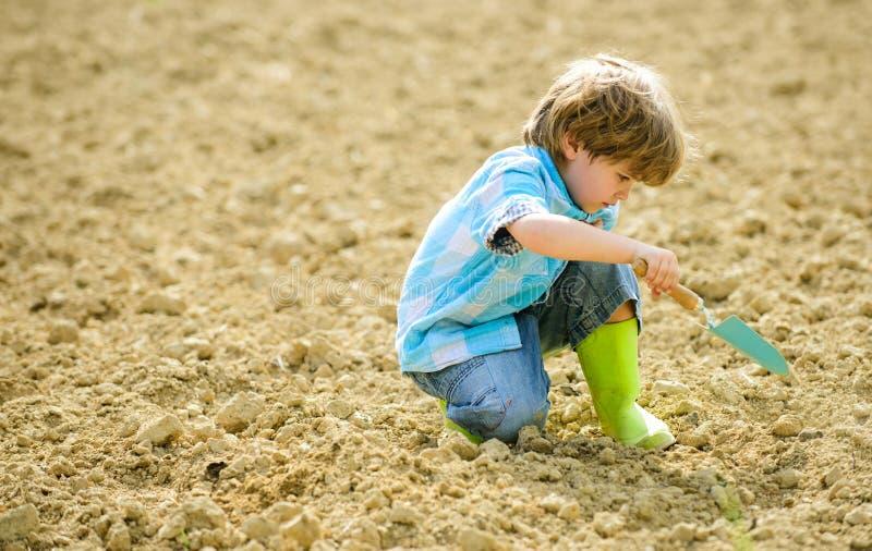 Lantbruk och jordbruk liten unge som planterar en blomma Ekologiliv Odlingbegrepp brown r?knad dagjord som milj?l?vverk g?r den g royaltyfria bilder