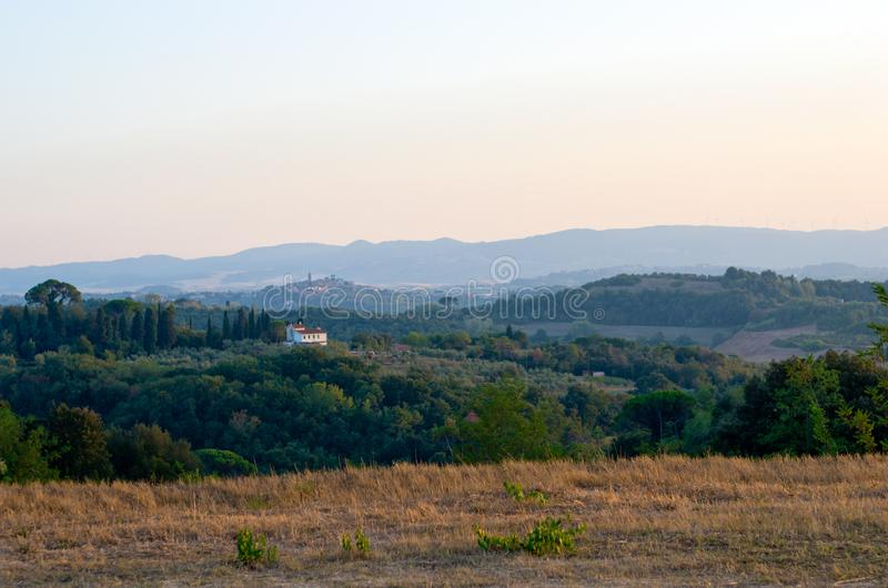 lantbrukarhem i den Tuscan bygden med den forntida lilla byn royaltyfri fotografi