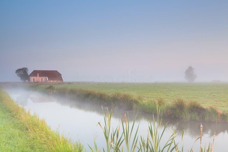 Lantbrukarhem på flodstranden i morgondimma arkivfoto