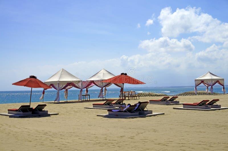 Lanterfanterstoelen en parasols op een zandstrand in Bali royalty-vrije stock foto's