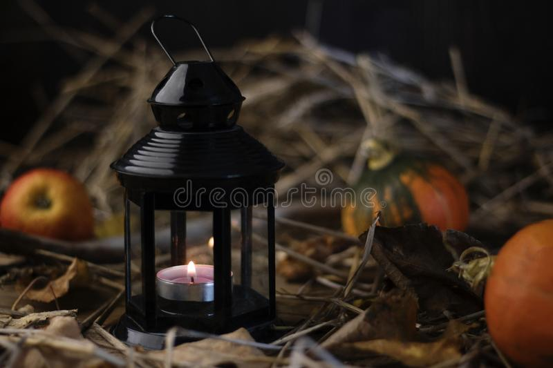 Lantern on a background of hay, fallen leaves, pumpkins and apples. Burning candle. Autumn background. stock images