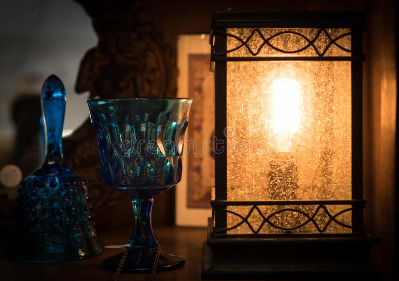Lantern with Blue wine glass and dinner bell illuminated by light from lantern royalty free stock photography