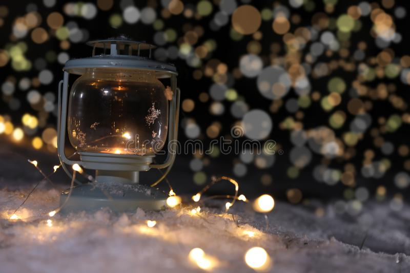 Lantern with burning candle and Christmas lights on snow against blurred background, space for text. Winter decor stock image