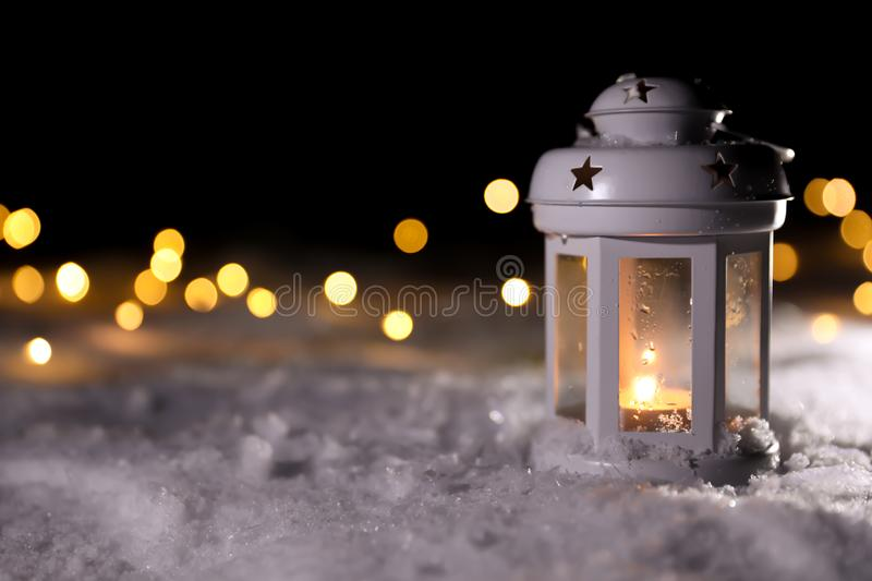 Lantern with burning candle and Christmas lights on snow outdoors. Space for text. Lantern with burning candle and Christmas lights on white snow outdoors. Space royalty free stock photos