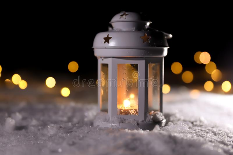 Lantern with burning candle and Christmas lights on snow outdoors. Space for text. Lantern with burning candle and Christmas lights on white snow outdoors. Space royalty free stock photography
