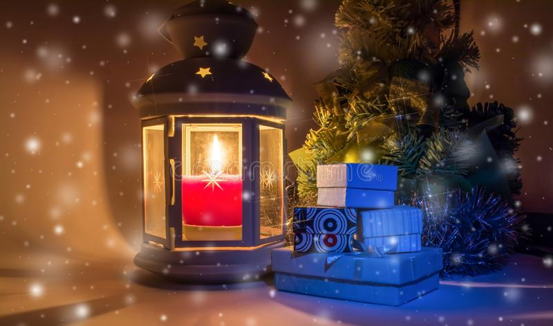 Christmas tree with gift boxes and old vintage lantern with burning candle and with a beautiful shine as a star on a falling snow royalty free stock images