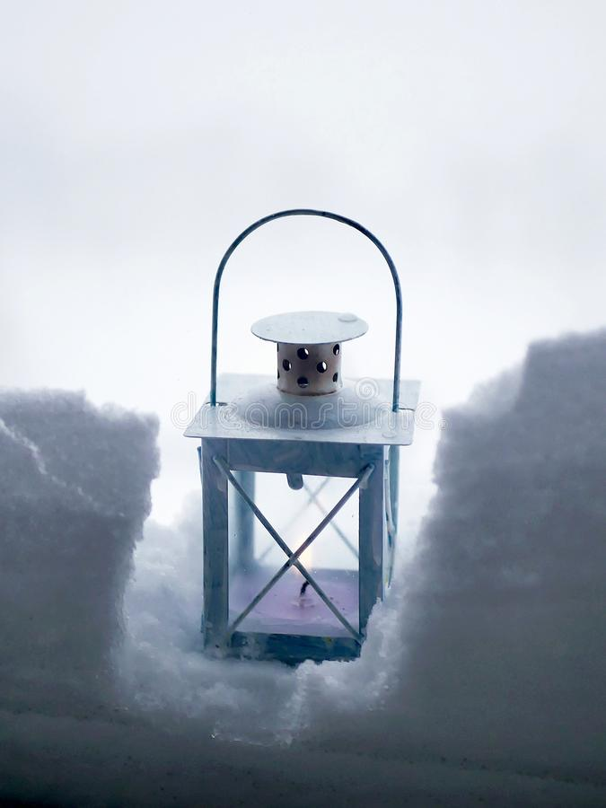 A lantern with a burning candle in the snow against the backdrop of a winter landscape, bad weather stock photos
