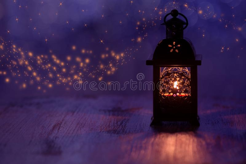 Lantern with candle on a beautiful blue background with stars. Christmas background . stock image