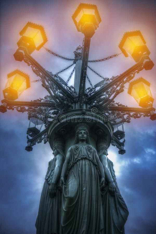Lantern with caryatids shines at night. Prague royalty free stock photo
