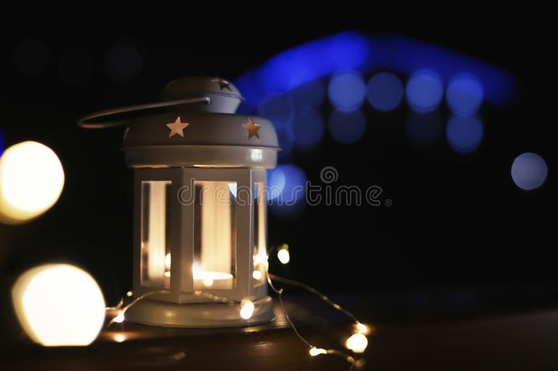 Lantern and Christmas lights on wooden railing against blurred background, space for text. Winter night. Lantern and Christmas lights on wooden railing outdoors royalty free stock photography
