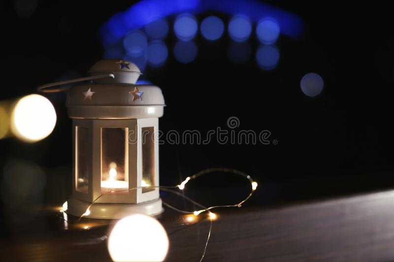 Lantern and Christmas lights on wooden railing against blurred background, space for text. Winter night. Lantern and Christmas lights on wooden railing outdoors royalty free stock photo