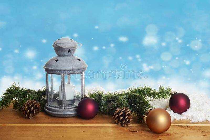 Lantern with christmas ornaments on wood with snow royalty free stock image