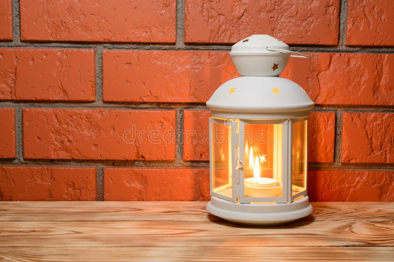 A lantern with a glowing candle in on the wooden table, brick wall background stock images