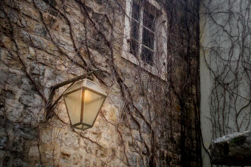A lantern illuminates a stone wall with a small white window in the old town royalty free stock photos