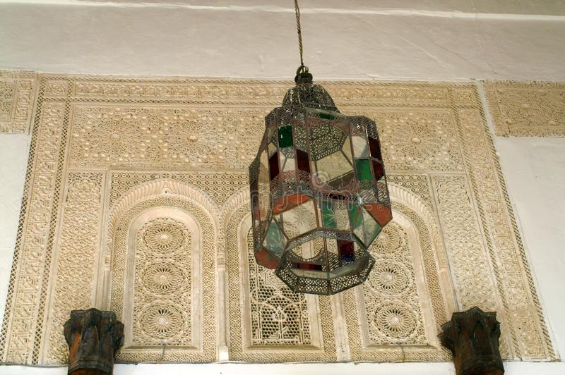 Lantern of metal and colored glass in an Arab building. Tangier. Morocco. Wall with Arabic carvings on the stone. The wall is decorated with stone ornament royalty free stock image