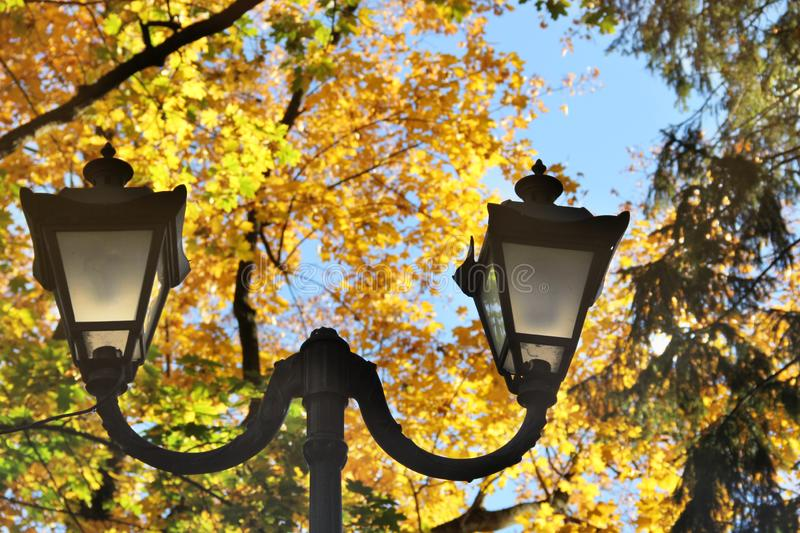 Lantern in the park on the background of yellow trees. Autumn stock images