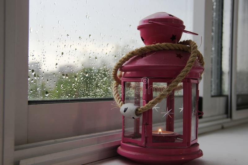 Lantern pink with a burning candle at home on a window on a rainy summer day. autumn, the raindrops on the glass. Lantern pink with a burning candle at home on a stock photos