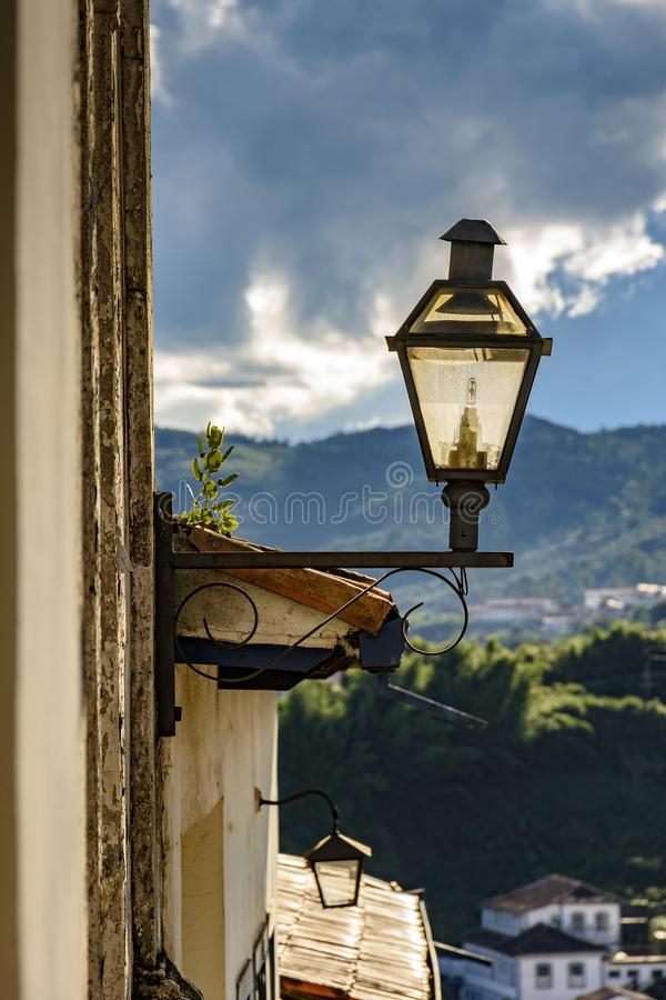 Lantern stuck to the facade of an old colonial-style house. During the late afternoon of the city of Ouro Preto in Minas Gerais stock images