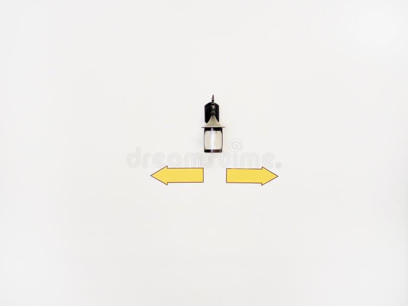 Lanterna com os sinais que apontam em sentidos diferentes na parede branca com copyspace fotografia de stock royalty free