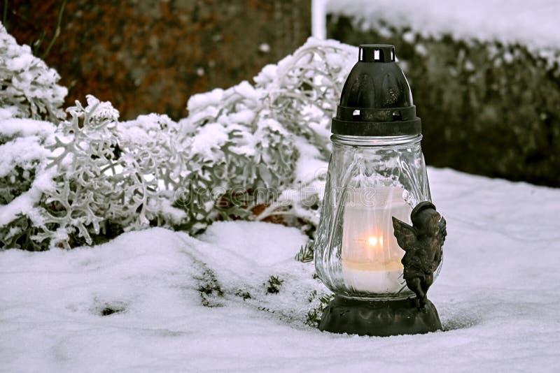Lanterna con la candela alla tomba coperta di neve nell'inverno immagine stock libera da diritti