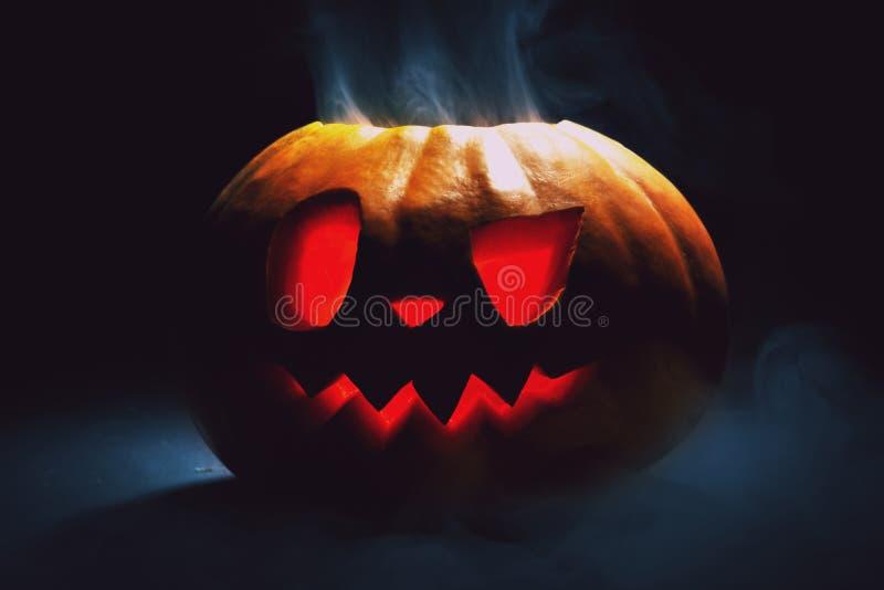 Lanterna da abóbora de Dia das Bruxas com as folhas secas com olhos ardentes fotografia de stock