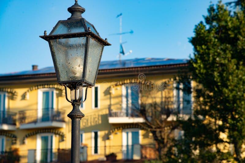 A lanterna da rua com vidro branco e a casa bonita muram o fundo imagem de stock