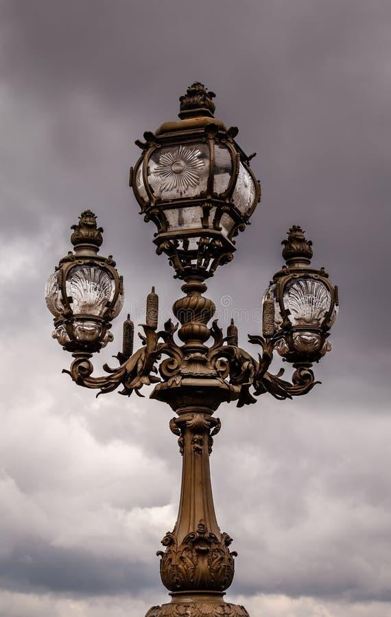 Lanterna da rua na ponte de Alexandre III contra o céu nebuloso imagens de stock