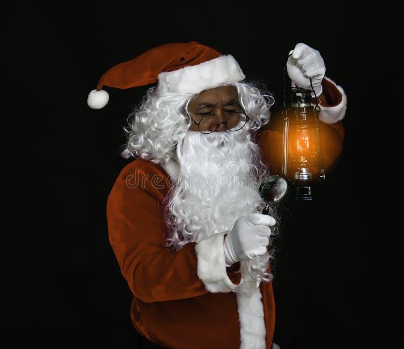 Lanterna da terra arrendada de Santa Claus para iluminar o tiro do estúdio no fundo preto para a família, dando, estação, Natal,  imagem de stock royalty free