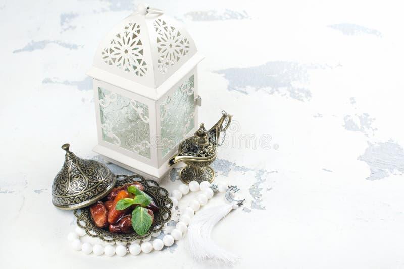Lanterna, datas, lâmpada de aladdin e rosário árabes no fundo branco foto de stock