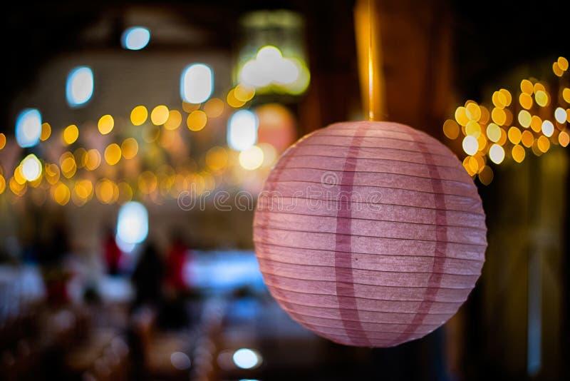 A lanterna de papel/quinquilharia que pendura para dentro, com bokeh ilumina-se atrás fotografia de stock