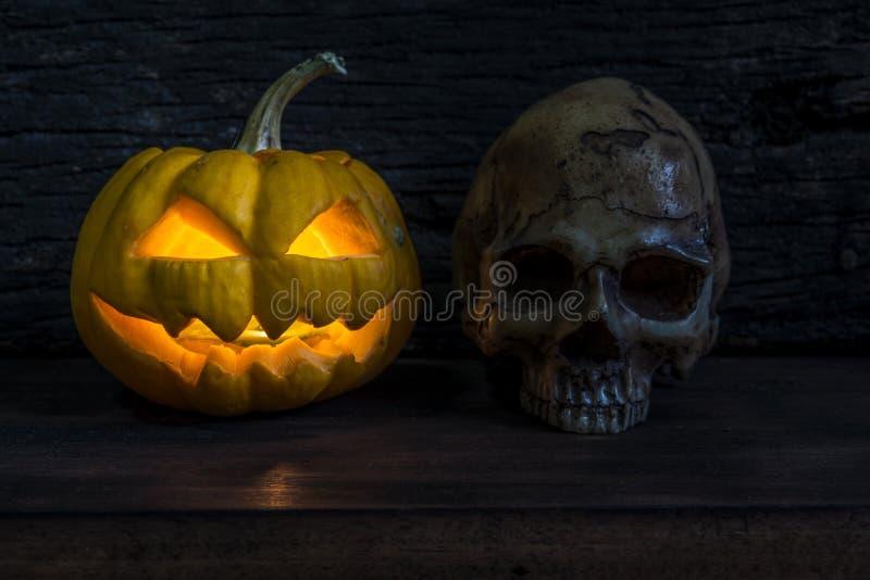 Lanterna della presa della testa della zucca di Halloween con il cranio umano immagine stock