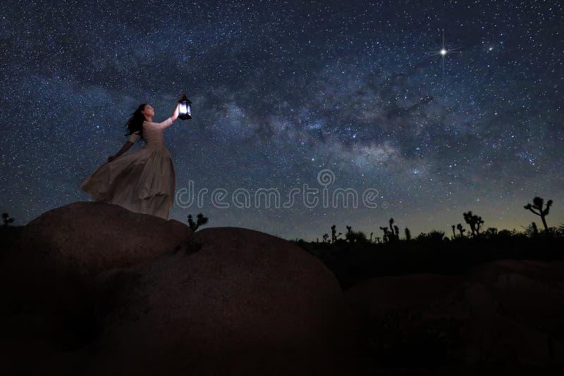 Lanterna della tenuta della ragazza nel deserto in corso la Via Lattea fotografia stock libera da diritti