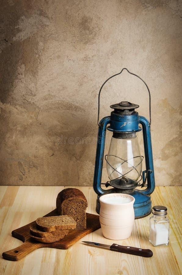Lanterna di cherosene, tagliere, vaso di argilla con latte, pane di segale e sale su una tavola di legno fotografie stock libere da diritti