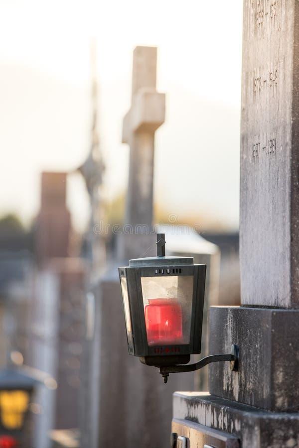 Lanterna e cruz de pedra no cemitério, pôr do sol, licença fotos de stock