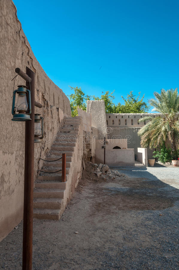 Lanterna e ruínas da parede do forte de Nizwa, Omã imagens de stock