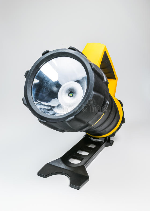 Lanterna elétrica amarela grande à mão com o ângulo ajustável isolado no fundo branco fotografia de stock royalty free