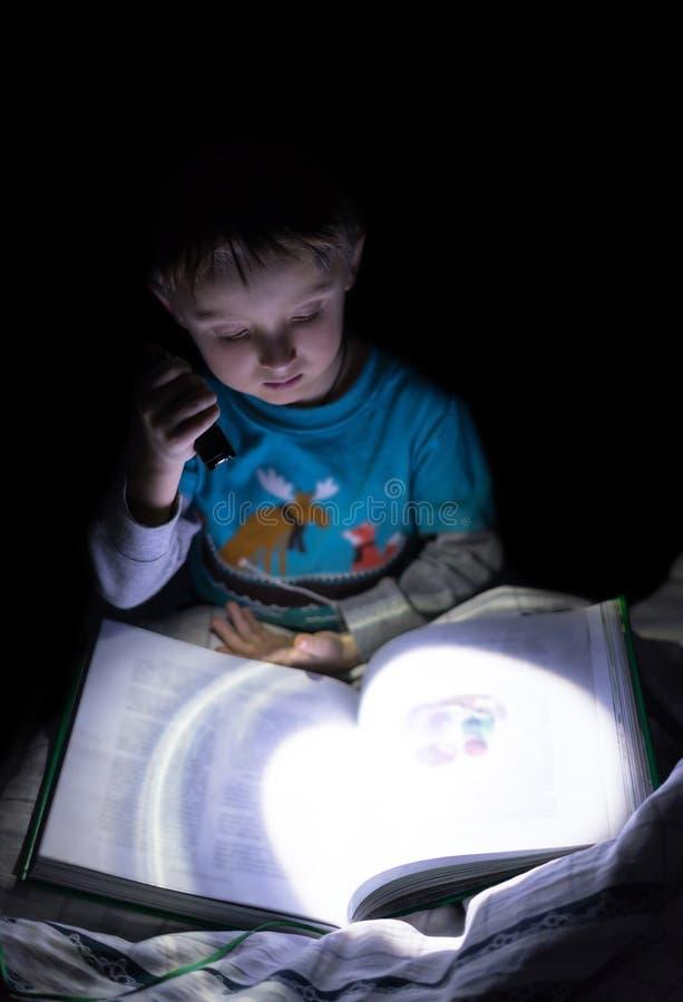 A lanterna elétrica está no foco, menino é borrada Menino caucasiano do divertimento que lê um livro na noite com a lanterna elét fotos de stock