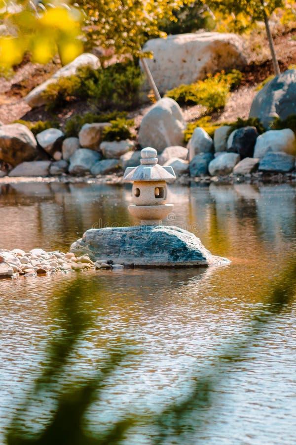 Lanterna japonesa empoleirada em uma rocha no meio de uma lagoa nos jardins de Frederik Meijer em Grand Rapids Michigan fotografia de stock royalty free