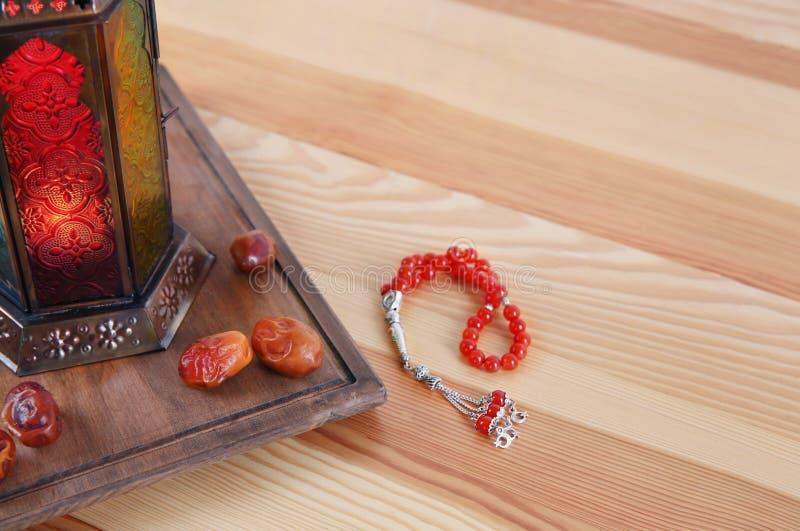 Lanterna musulmana Fanous, datteri secchi e perle di preghiera sulla tavola di legno fotografie stock libere da diritti