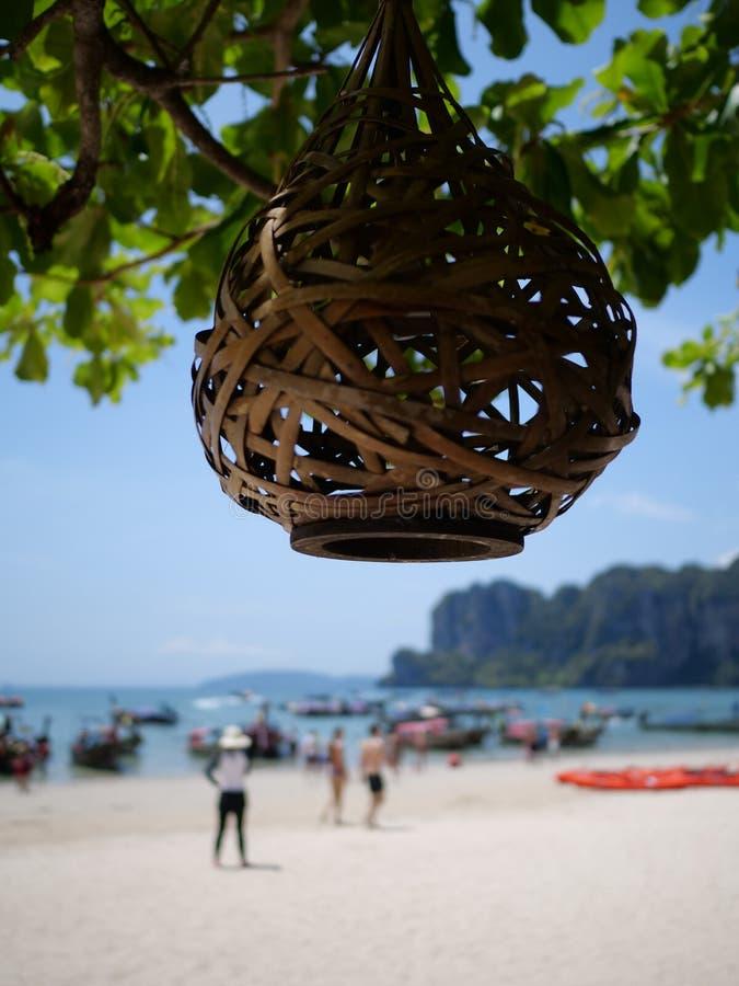 A lanterna na árvore sobre silhuetas borradas dos povos na praia fotos de stock royalty free